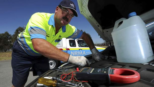 CHECK-UP: NRMA patrolman Jason Venn works to repair an overheated vehicle in Tuggeranong on Monday.