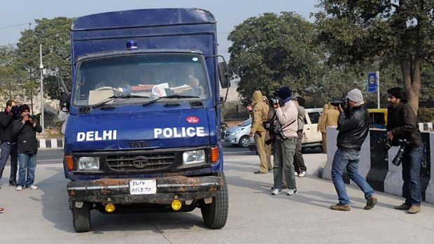 Police drive the vehicle believed to be carrying the accused in a gangrape and murder case.