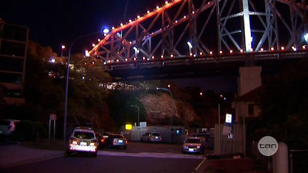 Police gather at the base of cliffs at the Story Bridge.