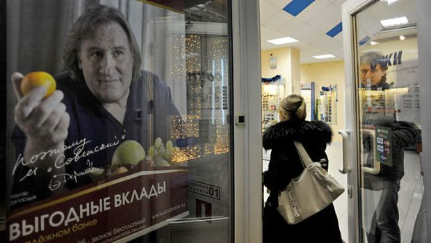 People pass by an advertisement poster of a small Russian bank showing Gerard Depardieu. Russians reacted with ...