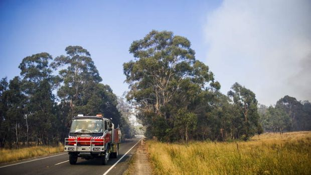 The scene from the Kings Highway. Crews work to contain fires near Bungendore.