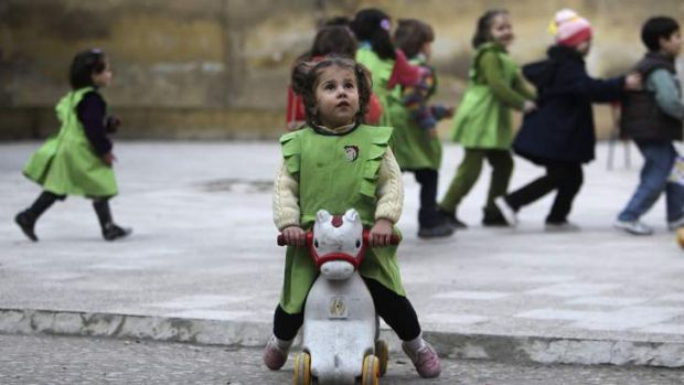 A girl looks up to the sky after hearing the sound of shelling near her school in Aleppo.