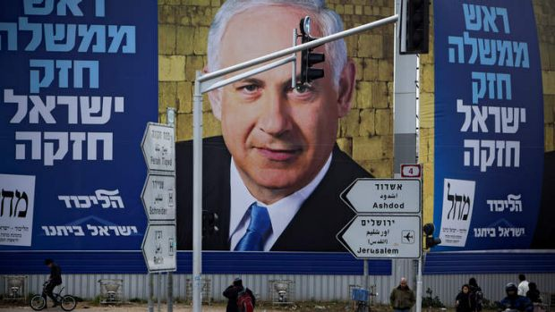 Last days ... Israelis walks past a picture of the Israeli Prime Minister Benjamin Netanyahu, whose party is facing ...