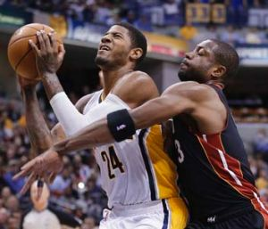 Paul George of Indiana (24) is fouled by Dwyane Wade of Miami.