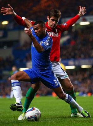 Ashley Cole of Chelsea is closed down by Danny Graham of Swansea City.