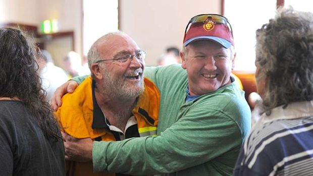 Two men embrace at a community meeting at Snake Valley Community hall.