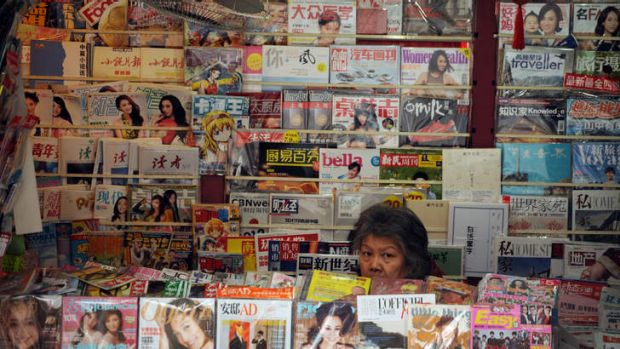 War of words . . . a newspaper vendor looks out from her booth on a street in Shanghai.