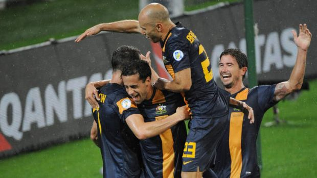 Alex Brosque is mobbed by Socceroo teammates.