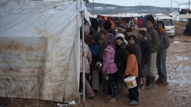 Syrian refugee children wait in freezing conditions for their familie's daily food ration at a refugee camp in Bab ...