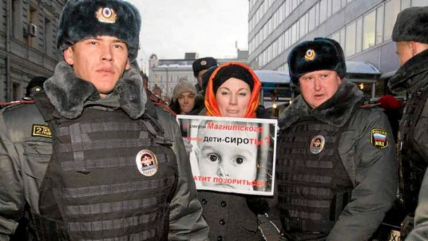 Russian police detain a protester against the ban on adoptions to the US.