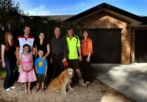 Lara and the Davidson family, in front of their rebuilt house last January.