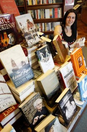 Paperchain Bookstore Manuka senior staff member Rose Ward restocks some of the Christmas best sellers.