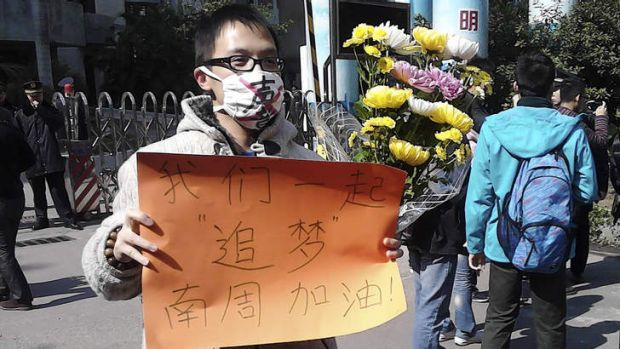 """A man wearing a mask with words """"Silent"""" holds a banner reading 'Let's chase our dreams together, go <i>Southern ..."""