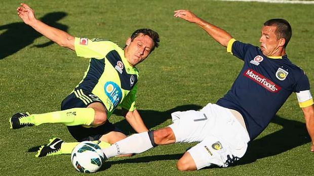 Victory's Mark Milligan challenges John Hutchinson of the Mariners during Saturday's A-League match.