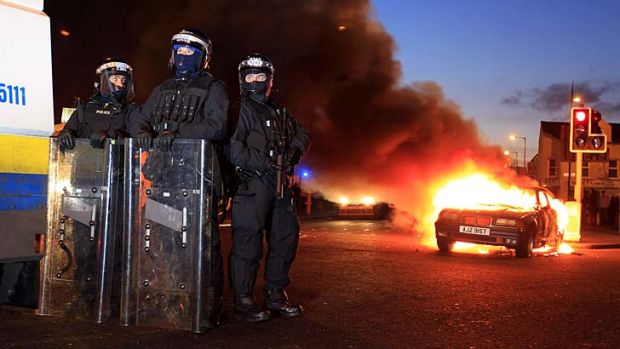 Anger unabated … police officers in riot gear stand near a burning hijacked car during continued clashes in East ...