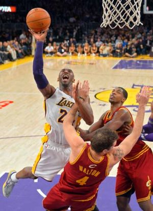 Los Angeles Lakers guard Kobe Bryant goes up for a shot as Cleveland Cavaliers forward Luke Walton (centre) falls and ...