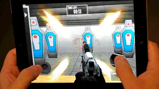 """A man playing the newly released National Rifle Association  iPhone/iPad app """"NRA: Practice Range''."""