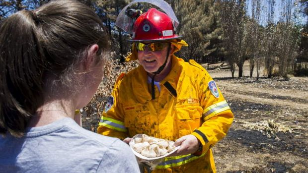 Bungendore RFS Captain, Sheldon Williams, accepts a plate of home-made meringues from Jacqui Coleman after extinguishing ...