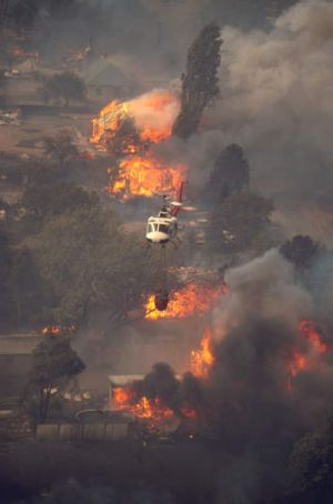 A helicopter waterbombs houses burning at Uriarra at about 1.30pm on January 18, 2003.