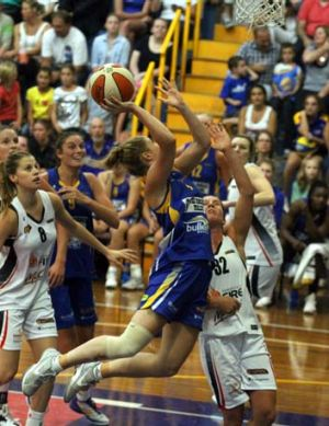 Stretched: Boomer Rebecca Cole leaps over a Townsville opponent in an attempt to score at the Veneto Club on Saturday night.