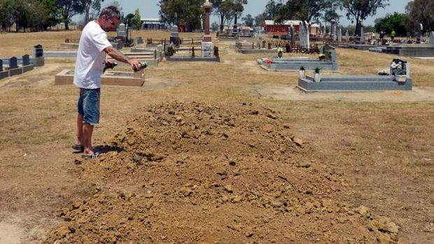 A man pours beer on the mounds of dirt where Ned Kelly was buried on Sunday at the Greta cemetery.