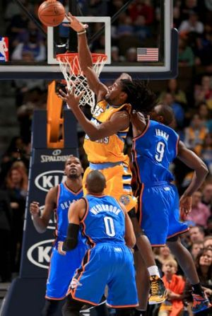 Kenneth Faried (35) of the Denver Nuggets grabs a rebound away from Serge Ibaka (9), Kevin Durant, and Russell Westbrook ...