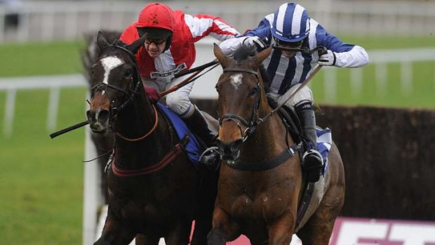 A nag comes good ... Paul Carberry riding Monbeg Dude (left) clears the last hurdle before claiming the Welsh Grand National.