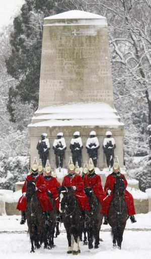 Members of The Household Cavalry Mounted Regiment ride along Horse Guards Parade during a snow flurry.