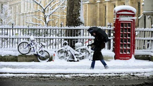 A woman walks through the snow as she makes her way through central London in heavy snow.