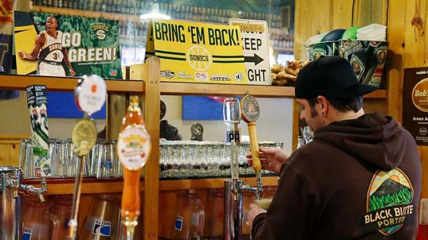 """Christian Adametz, owner of Floyd's Place in Seattle, pours a beer for a customer next to a sign that reads """"Bring 'Em ..."""