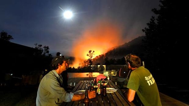 Fires in the Alpine National Park at Harrietville. Justin Crawley (left) watches the fire with Andy Forbes after ...