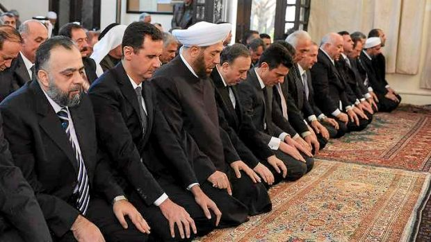 In this image supplied by Syria's state news agency SANA,  President Bashar al-Assad (second from left) prays during ...
