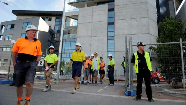 CFMEU Secretary Dean Hall (right) stands at the Aurora apartments this morning as workers are ordered off the site, so a ...