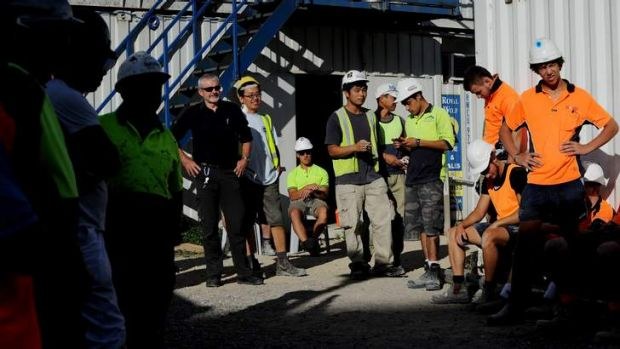 Norman MacLachlan, ACT construction manager for Project Coordination (black shirt) stands with his workers  from the ...