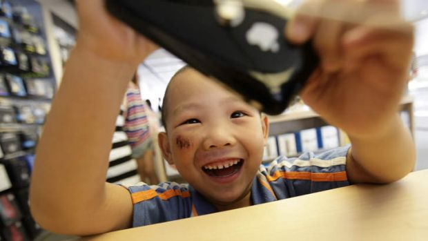 A 5-year-old boy plays games on an iPhone in Apple's flagship store in Beijing.