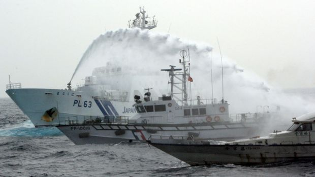 A Japanese Coast Guard patrol boat sprays a water cannon over a Taiwan Coast Guard boat to warn a Taiwanese leisure boat ...
