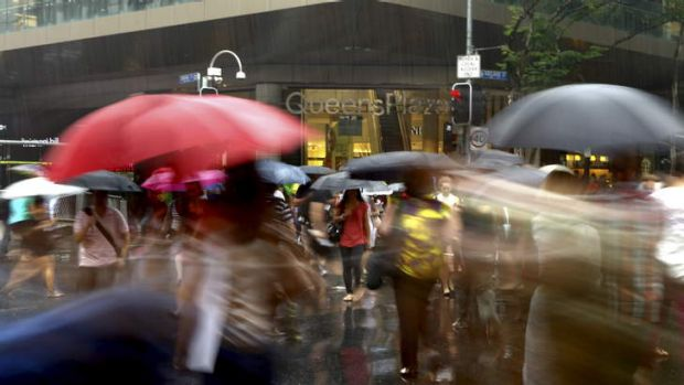 People dodge the rain on Friday afternoon in the Brisbane CBD ahead of a forecasted wet weekend.