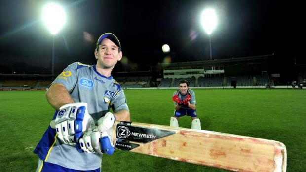 ACT Comets batsman Aaron Ayre and wicketkeeper Beau McClintock under the new lights at Manuka Oval.