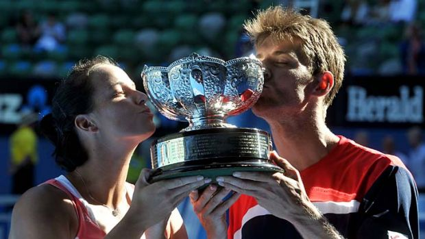 Matthew Ebden and Jarmila Gajdosova with their trophy. Behind them, the stands are virtually empty.