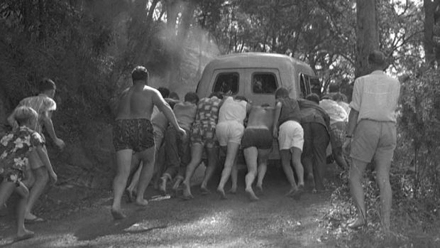 Helpers try unsuccessfully to push the broken-down vehicle up a steep incline.