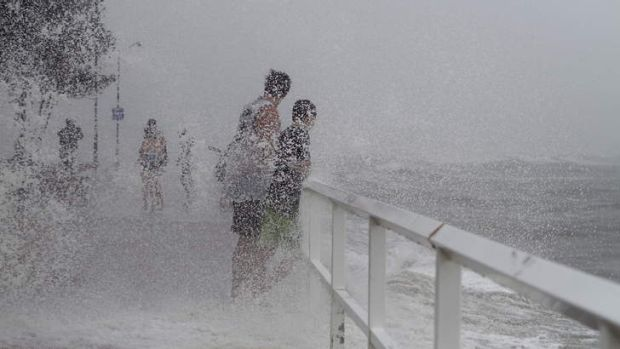 Locals at Shorncliffe Pier near Brisbane check out the storm surge during the cyclonic conditions affecting the coast of ...