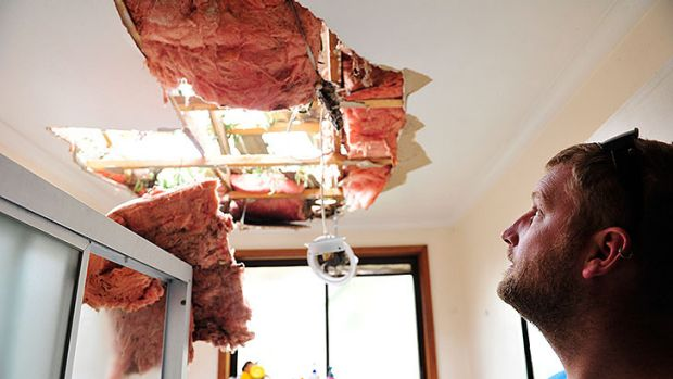 Greg Sutherland inspects the damage to the household bathroom that was caused by a tree, pushed over by destructive ...