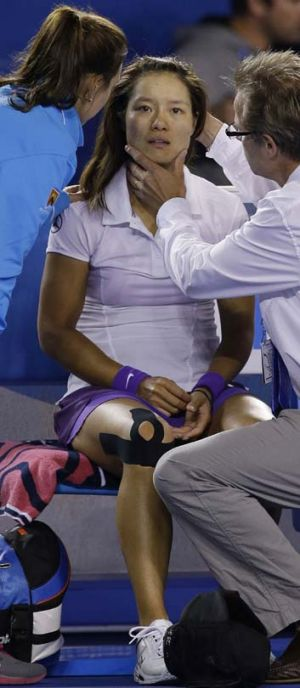 Concussion check … Li Na is treated after falling following the fireworks break.