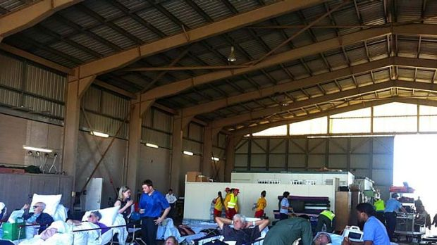 Patients evacuated from Bundaberg Hospital wait to board Hercules running airlifts to Brisbane.