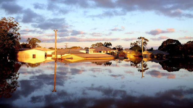 The sun rises over flooded streets as parts of southern Queensland experiences record flooding in the wake of Tropical ...