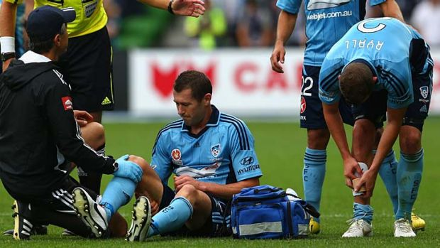 Down and out … Brett Emerton is treated for an injury during Saturday's match against Melbourne Victory.