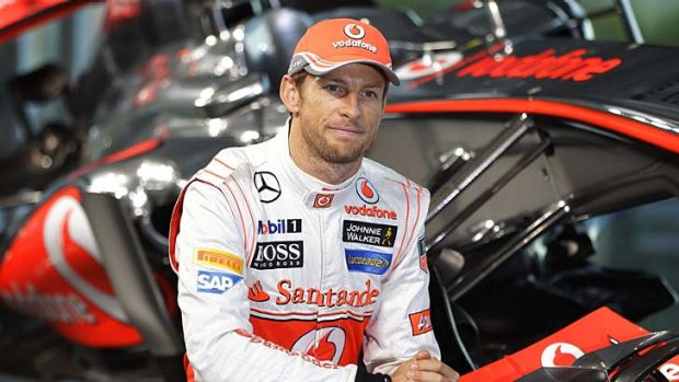 McLaren Mercedes F1 driver Jenson Button poses with the newly unveiled MP4-28 car, prior to the launch, at McLaren ...