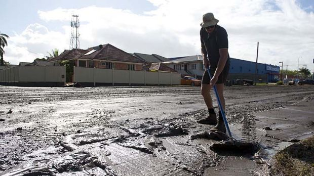 A man cleans up mud days after flooding in Bundaberg.