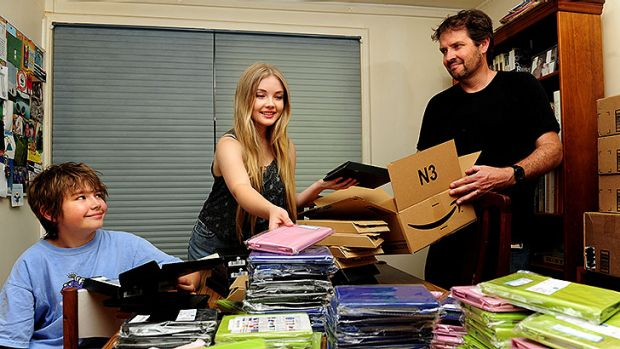 Daniel Billing and his children Luka,10 and Hannah,16 packing kindles to send to indigenous children all over the ...
