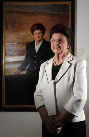 Imelda Roche stands in front of her portrait by Paul Newton.